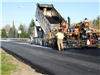 The final layer of asphalt is placed on River Road