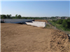 Completed soil embankment at Bypass 4 bridge over railroad awaits the construction of bridge abutments