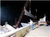 A crane hoists the first steel beam into place for the new bridge