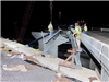 Workers install steel beams for the new bridge over railroad tracks