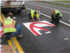 Fairfield's resident sign craftsmen, Wes and Jason, install the pre-formed thermoplastic pavement markings for No Thru Trucks in the lanes that lead to Ross Road