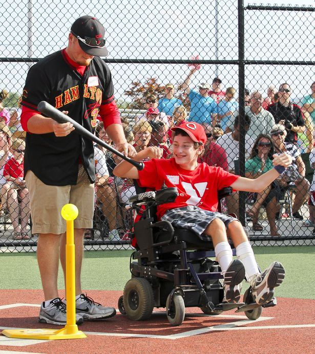 Child hitting a ball with assistance for miracle league play