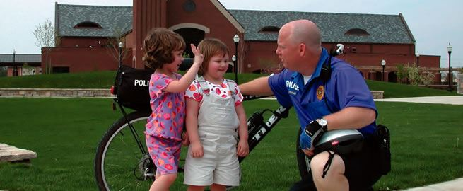 Bike cop speaking with 2 little girls.