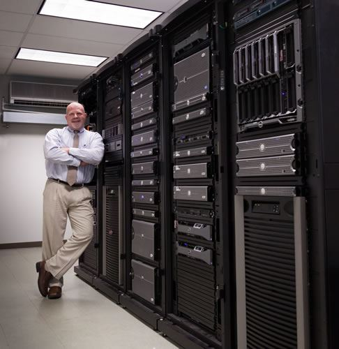 Joseph Waldmann standing next to large devices and server of Information Technology Division