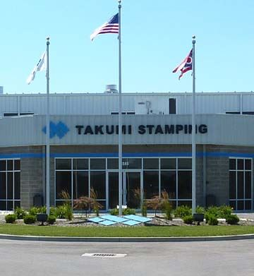 Takuhi Stamping building with flags and flag poles in front of building